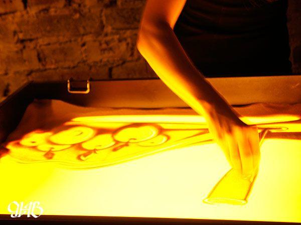 """Песочная анимация на презентации дегустационной комнаты магазина """"Крепкие напитки""""."""